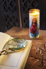 Deutsche Bibel auf altem Tisch mit Kerze