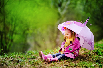 smiling little girl with umbrella in the park