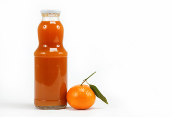 Juice in a glass bottle and tropical fruit on a white background