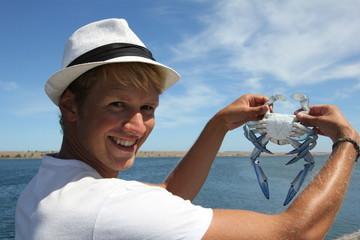 Jeune homme avec un crabe bleu