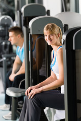 Two people at fitness center exercise machine