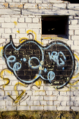 Graffiti paint on abandoned building brick wall