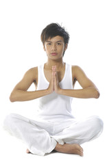Young man practicing yoga in white clothes