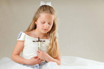 girl in communion dress with crucifix and eyes closed