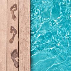 Traces de pieds nus au bord d'une piscine