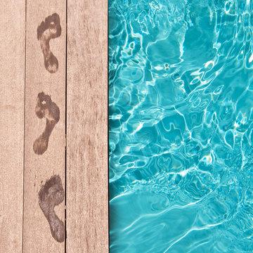 Traces de pieds nus sur un deck en bois,au bord d'une piscine, concept été