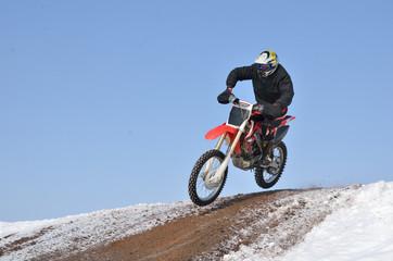 Motocross racer flying down the mountain