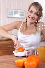 Blond woman freshly squeezing orange juice