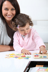 Mother with daughter doing puzzle