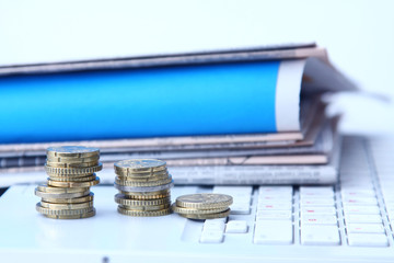 coins and paper on laptop