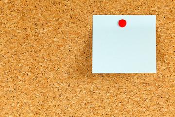 Korktafel mit Notizzettel und roter Reißzwecke