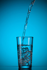 water pouring into glass on blue