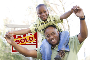 Father and Son In Front of Real Estate Sign