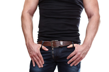 Muscular male torso in black t-shirt with hands on jeans