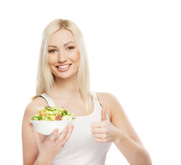 A young blond woman holding a fresh green salad