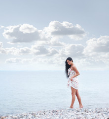 A young woman in a beautiful dress walking near the sea