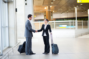 young businessman and businesswoman meeting at airport