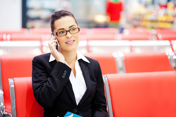 young businesswoman talking on cell phone at airport