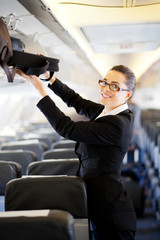 businesswoman putting her luggage into overhead locker
