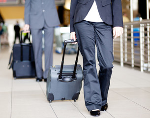 passengers walking in airport with luggages