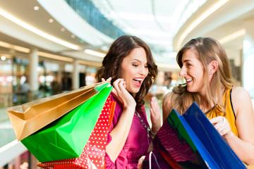 Zwei Freundinnen beim Shoppen in einer Mall