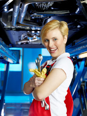 Apprentice for motor mechanic in a garge with her work tools