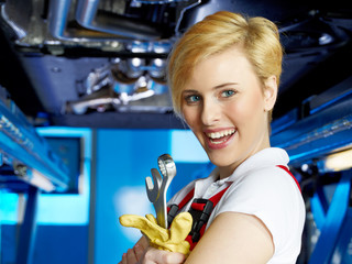 Pretty girl is proud of her apprenticeship in a garage