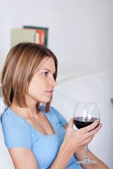 frau sitzt mit einem glas rotwein auf dem sofa