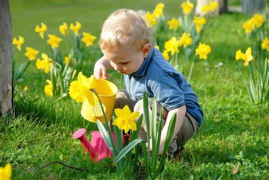 Blond child watering plants