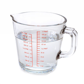 Water in glass measuring cup isolated on white background