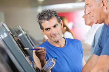 Fitnesstrainer erklärt Mann Laufband