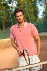 Handsome male tennis player smiling