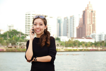 Young pretty Asian calling by phone with building background