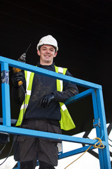 portrait of standing construction worker holding electric tool