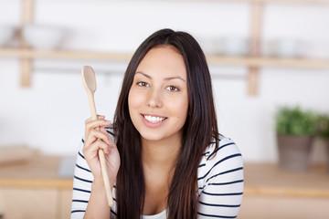 portrait junge frau mit kochlöffel in der küche