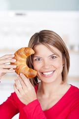 lachende frau zeigt croissant