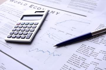 A calculator and a pen over documents, closeup