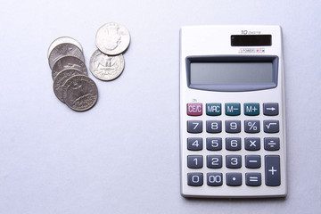 A calculator and coins on the table, from above