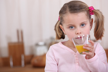 A little girl drinking orange juice in the kitchen.