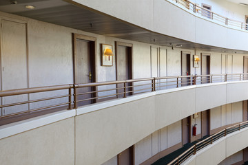 Stories in large hotel, grey balconies and rows of doors