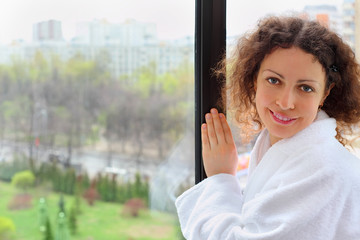 Smiling woman dressed in white bathrobe stands near window