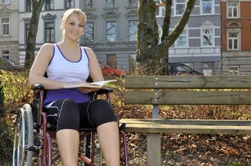 Rollstuhlfahrerin liest Buch