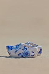Blue and white Dutch souvenir clogs on the beach