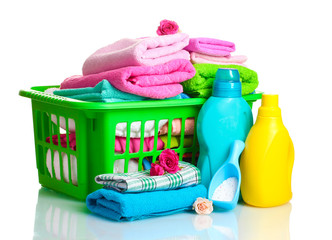 Detergents and towels in green plastic basket isolated on white