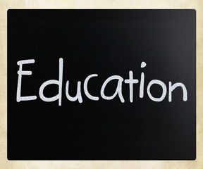 "The word ""Education"" handwritten with white chalk on a blackboar"