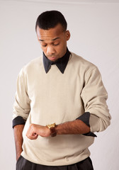Young black man in sweater looking at his watch