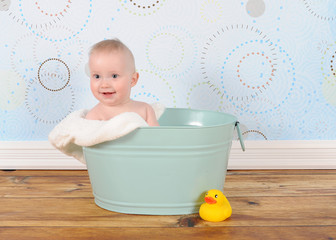 handsome baby boy sitting in washtub