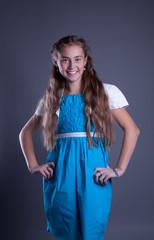 teen girl in a blue dress posing in studio