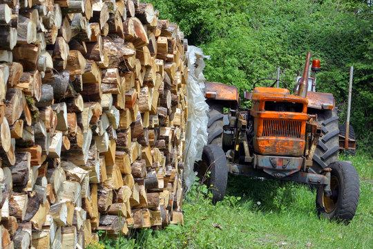 tracteur garé devant une pile de bois de chauffage