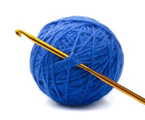 Ball of blue yarn and crochet hook